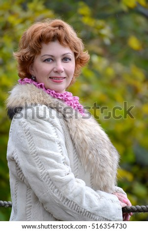 Portrait of the happy woman of average years against the background of autumn trees. Close up