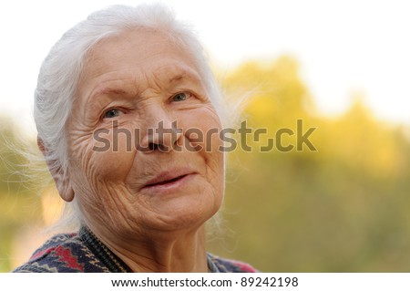 Portrait of the laughing elderly woman. A photo on outdoors