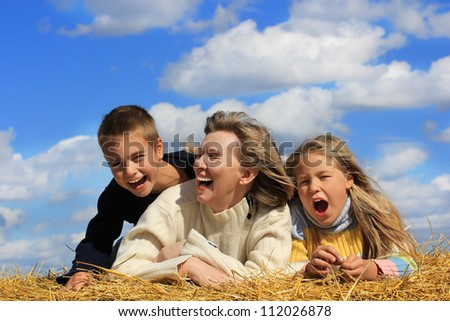 Portrait of the laughing  middle aged mother , little daughter and son on blue sky background . - stock photo