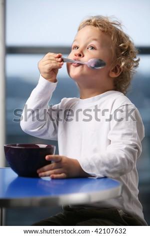 Portrait of the little boy eating yogurt. - stock photo