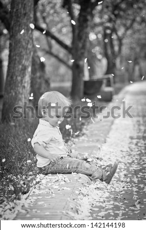 portrait of the little boy in the spring in park, a black-and-white photo