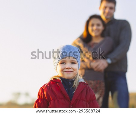 Portrait of the little girl with a funny hat outdoors and man and woman holding hands of smiling at the background. Family leisure outdoors concept - stock photo