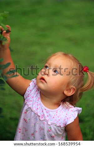 Portrait of the  little pretty  curious girl looking up - stock photo