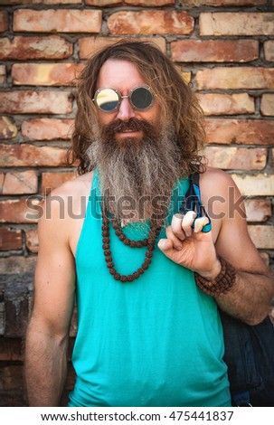 portrait of the man of hippie against the background of a brick wall