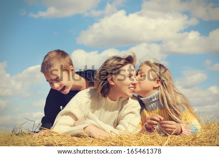 Portrait of the middle aged mother , little daughter and son on blue sky background - stock photo