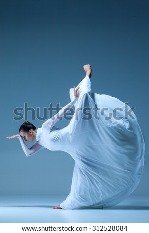 Portrait of the modern ballerina  in white dress on blue background - stock photo