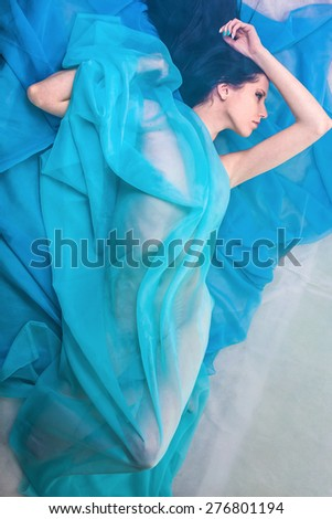 Portrait of the naked beautiful woman under a blue veil  - stock photo