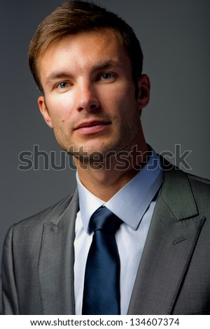 portrait of the nice businessman in a suit on a gray background - stock photo