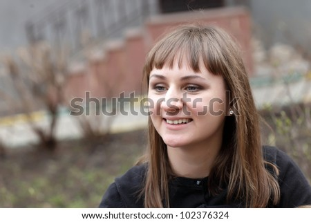 Portrait of the pretty smiling woman outdoor - stock photo