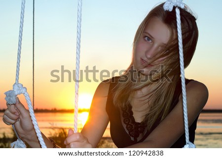 Portrait of the pretty teen girl at sunset