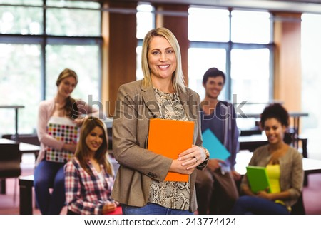Portrait of the professor with students behind her in libray - stock photo