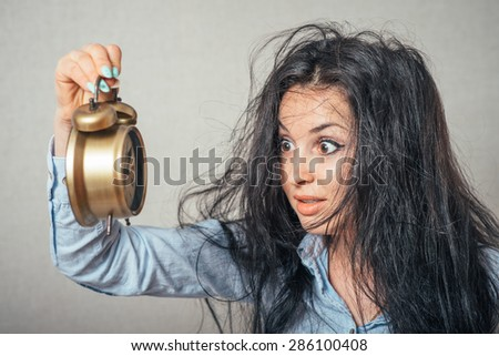 Portrait of the scared girl holding an alarm clock in a hand. - stock photo