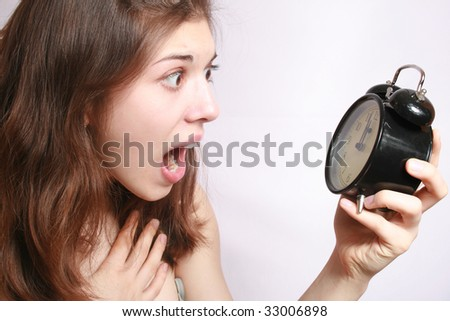 Portrait of the scared girl holding an alarm clock in a hand.