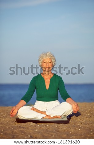 Portrait of the senior woman meditating on the seashore. Old woman relaxing by sea doing yoga. Meditation, yoga and relaxation concept. - stock photo