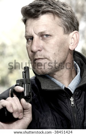 Portrait of the serious unshaven man with pistol. - stock photo