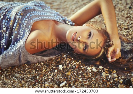 Portrait of the sexy woman on sea pebbles