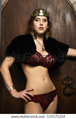 Portrait of the sexy woman wearing a crown in a medieval castle interior - stock photo
