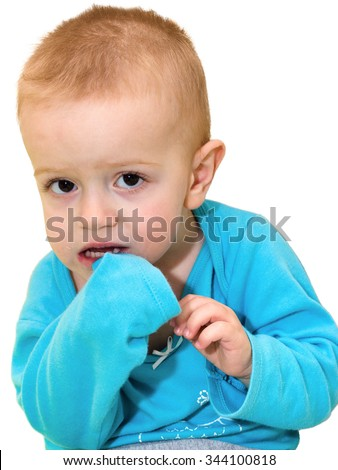 Portrait of the shriveled fair-haired kid in a blue t-shirt who is scaredly looking from below up. The isolated figure on a white background - stock photo