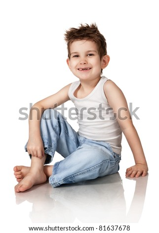 Portrait of the sitting boy in jeans on a white background