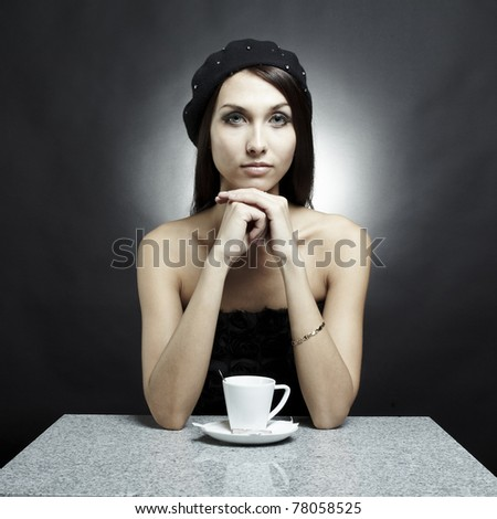 Portrait of the sitting young beautiful woman-brunette behind a table in cafe with a cup of coffee - stock photo