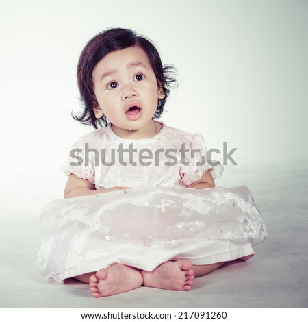 Portrait of the six month baby sitting happy and brother stand back on white background, process color - stock photo