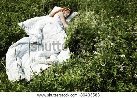 Portrait of the sleeping young woman on a meadow - stock photo