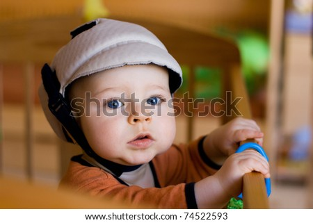 Portrait of the small happy child in a safety helmet standing in the bed - stock photo