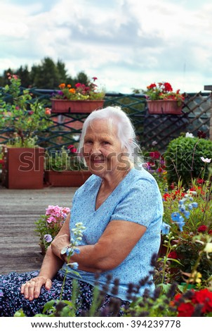 Portrait of the smiling elderly woman, in a garden - stock photo