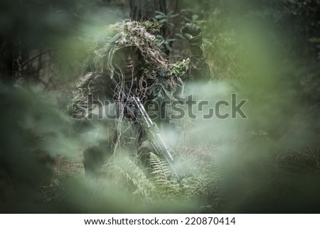 portrait of the soldier dressed in ghille suit, signaling stop in deep forest. rifle painted camouflage. face painted camouflage. - stock photo