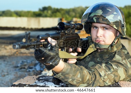 Portrait of the soldier in camouflage with machine gun - stock photo