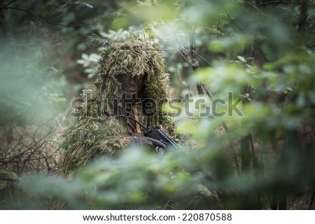 portrait of the soldier wearing ghille suit, face painted in camouflage, holding assault rifle. rifle painted black. - stock photo