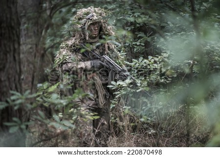 portrait of the soldier wearing ghille suit, holding assault rifle in deep forest. rifle painted camouflage. face painted camouflage. - stock photo