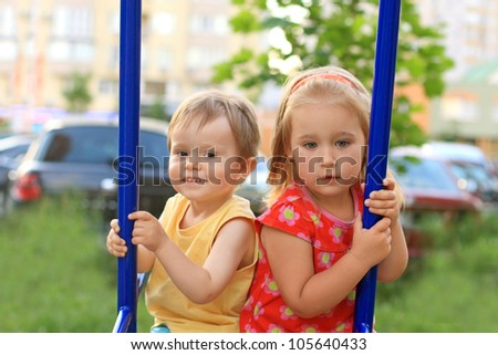 Portrait of the two kids sitting on the swing