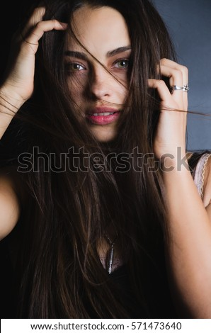 Portrait of the upper half of pretty young woman with swarthy skin, flying long dark hair, opened beautiful eyes and full lips. Studio. Low Key. Fashion. Beauty. Advertising. Headshot.