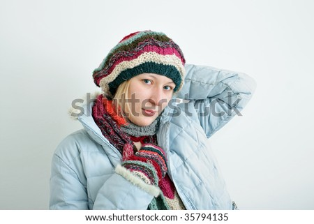 Portrait of the woman in a winter cap, mittens and a scarf.