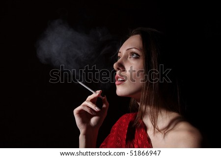 Portrait of the woman with a cigarette and a smoke against a dark background