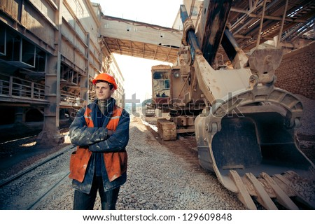 portrait of the working man in a helmet and work clothes near the excavator on a career - stock photo
