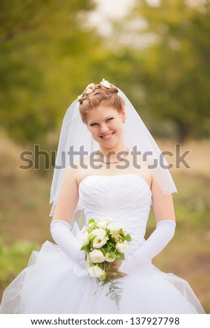 Portrait of the young beautiful bride on the nature - stock photo