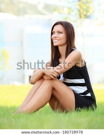 Portrait of the young beautiful smiling  business woman outdoors sitting on the grass.  - stock photo