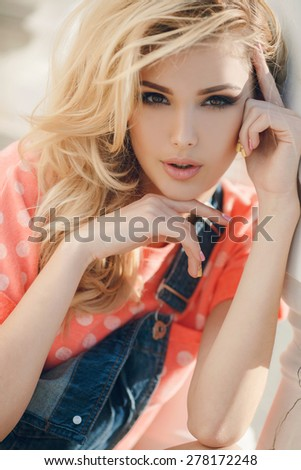 Portrait of the young beautiful smiling woman outdoors enjoying summer sun. Photo with instagram style filters. Young woman outdoors portrait. Soft sunny colors. Beautiful blonde woman outdoor - stock photo