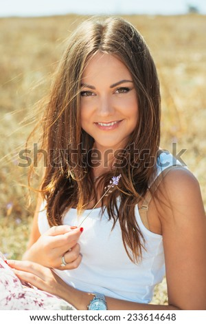 Portrait of the young beautiful smiling woman outdoors enjoying summer sun. wind in hair  - stock photo