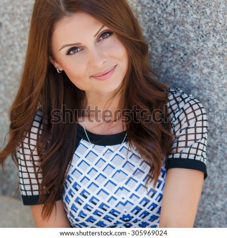 Portrait of the young beautiful smiling woman outdoors enjoying summer sun.Young woman outdoors portrait. Soft sunny colors. Beautiful brunette woman outdoor - stock photo