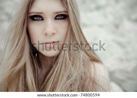 Portrait of the young beautiful woman outdoors with smoky eye makeup - stock photo