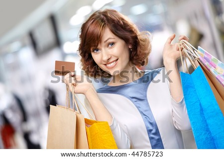 Portrait of the young beautiful woman smiling in shop with bags and a credit card - stock photo
