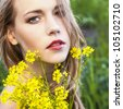 Portrait of the young beautiful woman with flowers - stock photo