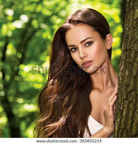 portrait of the young beautiful woman with long hairs. outdoors. - stock photo