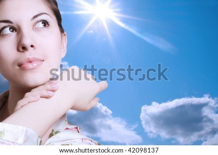 Portrait of the young brunette on a background of the sky with the shining sun.