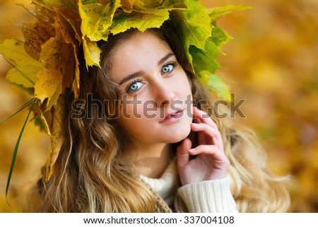 Portrait of the young girl dressed in a wreath at autumn time