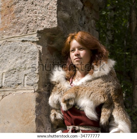 Portrait of the young girl in the Scandinavian historical suit on a ancient stone wall background - stock photo