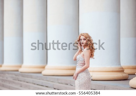 Portrait of the young girl with white skin. The young girl in an open dress in the summer on the street. The white girl with a beautiful make up and a hairstyle